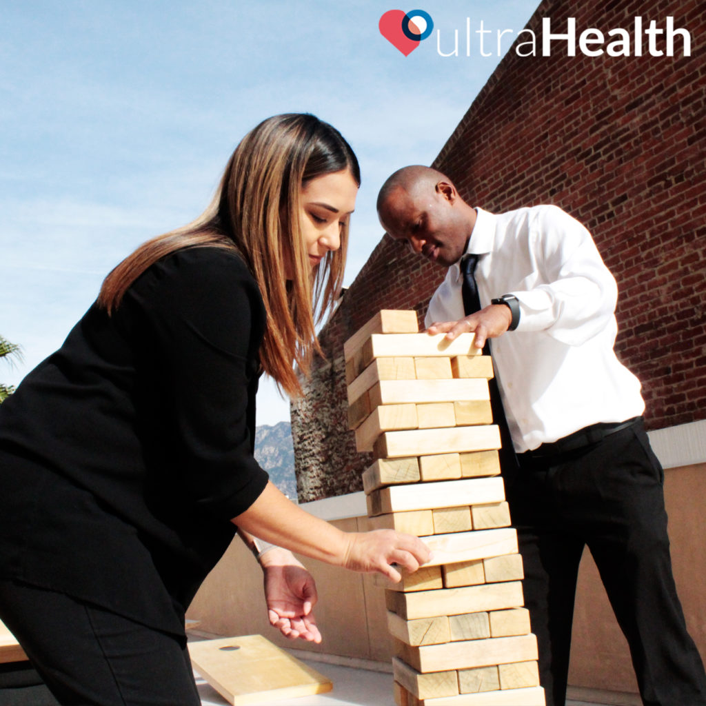 ultraHealth employees participating in team building exercises like Jenga